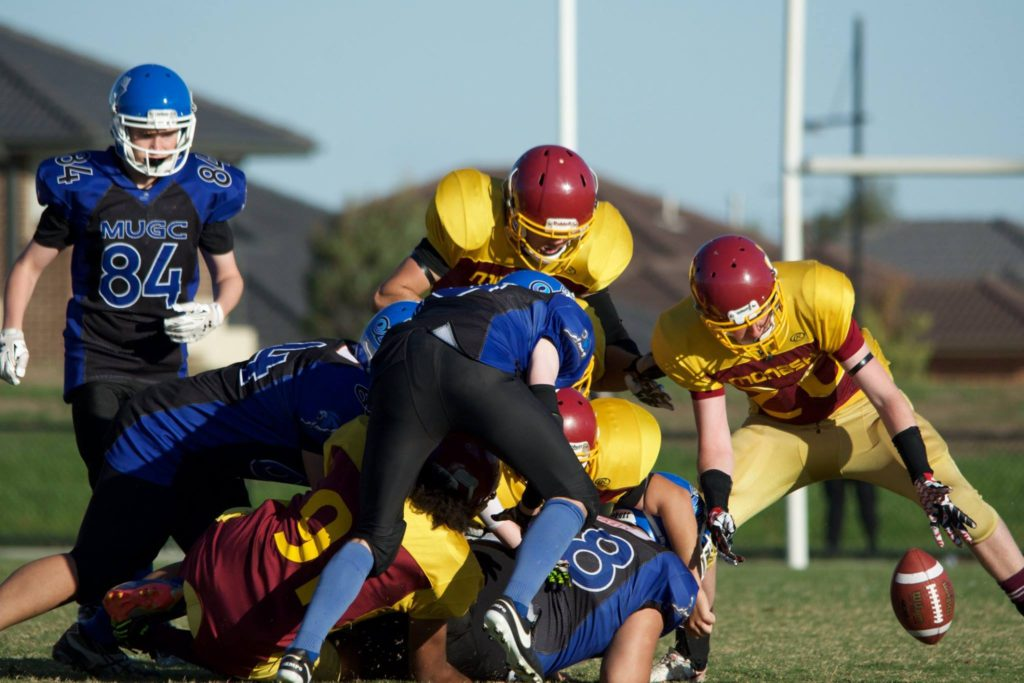 Jed Melican scoops up a fumble forced from a strip within the pile. (Photo courtesy of Bruce Rachon)